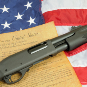 Gun Control -- Rifle lying over Constitution and flag